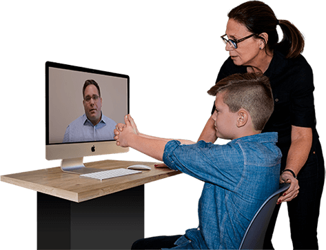 assistant with child receiving brain training exercises over the computer